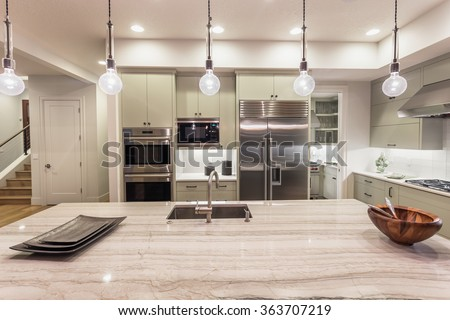 Kitchen with Island, Sink, Cabinets, and Hardwood Floors in New Luxury Home #363707219