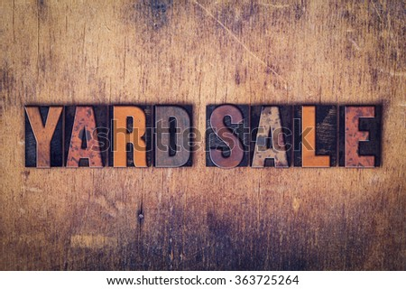 """The word """"Yard Sale"""" written in dirty vintage letterpress type on a aged wooden background."""