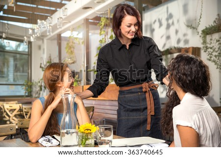 Friendly waiter server laughing smiling having fun with customer patron pretty modern Royalty-Free Stock Photo #363740645