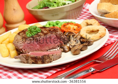 Rare fillet steak with chips, peas, mushrooms and onion rings. #36381556