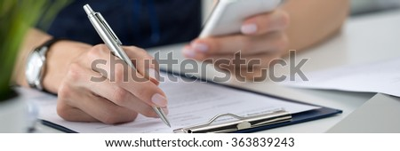 Close-up of female hands. Woman writing something and looking at mobile phone screen sitting at her office. Letter box format #363839243