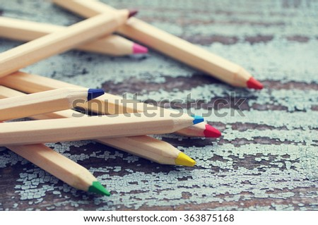 Colored wooden pencils on a wooden old background. Colored drawing pencils in a variety of colors on vintage wooden background #363875168