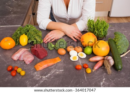 Woman in kitchen with different raw foods  Royalty-Free Stock Photo #364017047