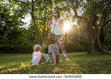 Two toddler boys sitting in a green grass looking at their mom blowing soap bubbles in a park under trees backlit by setting evening sun. #364056800