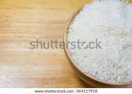 Rice in wooden bowl on Sack or wood table background #364117958