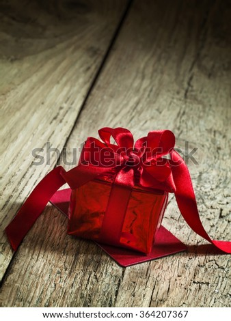 Red gift box tied with a scarlet ribbon with a bow on the old wooden background, standing on the red greeting card, selective focus #364207367