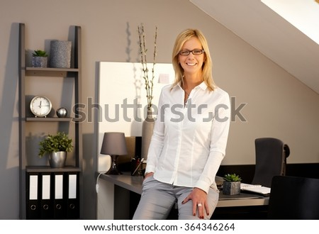 Happy blonde businesswoman smiling in office, looking at camera. #364346264