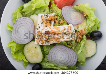fresh greek salad in white plate on wood table #364373600