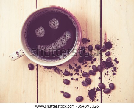 Espresso Cup with smiley face on wooden table, overhead view ,vintage color toned image
