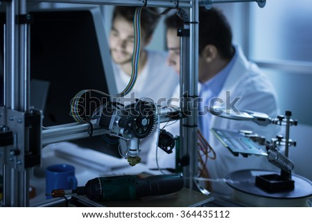 Young engineers working in the laboratory and using a computer, 3D printer on foreground, science and technology concept #364435112
