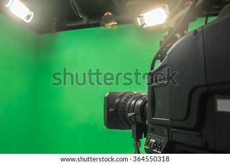 Television studio with camera and lights - camera on green screen #364550318
