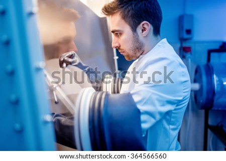 Scientist using protective robber gloves for handling dangerous substances in sterile environment #364566560
