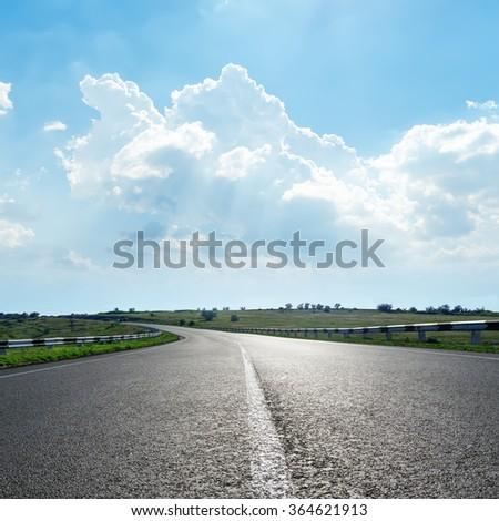 black asphalt road with white line under clouds in blue sky #364621913