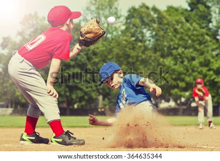Boy sliding into base during a baseball game with Instagram style filter #364635344