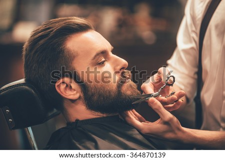 Getting perfect shape. Close-up side view of young bearded man getting beard haircut by hairdresser at barbershop #364870139
