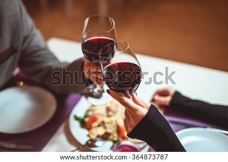 Beautiful young couple with glasses of red wine in luxury restaurant #364873787