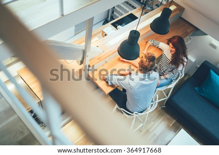 Beautiful couple talking in their pristine home while sitting at kitchen counter #364917668