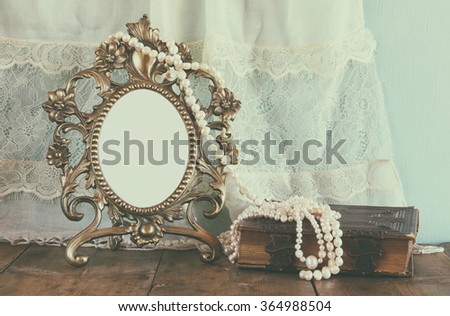 Antique blank Victorian style frame and old book with vintage pearl necklace on wooden table. retro filtered image. template, ready to put photography