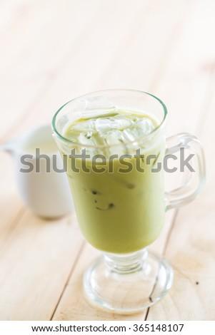 iced matcha latte on wood background #365148107