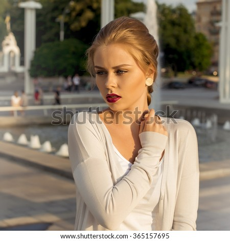 blonde young woman wearing fashionable clothes, white cardigan walking on the street . Fashion photo #365157695