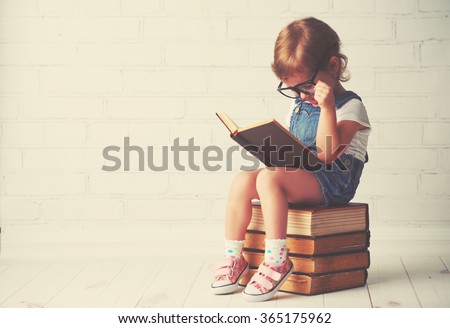 happy child little girl with glasses reading a books #365175962