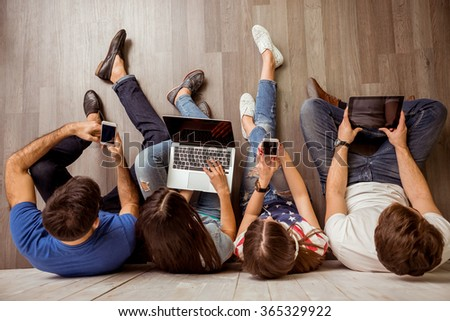 Group of attractive young people sitting on the floor using a laptop, Tablet PC, smart phones, headphones listening to music, smiling #365329922