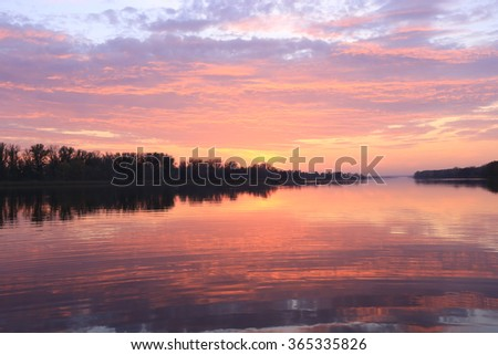 autumn landscape magnificent sunset over the river and reflected clouds in a mirror surface  #365335826