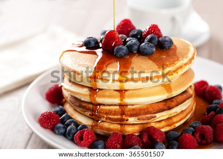 Pancakes with berries and maple syrup Royalty-Free Stock Photo #365501507