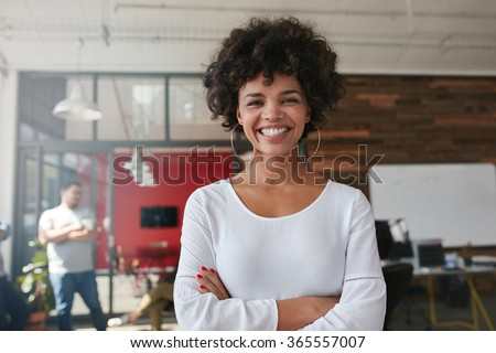 Smiling young woman standing with her arms crossed and looking at camera. She is standing in a modern office with her colleagues in the background. #365557007