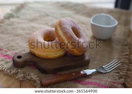 Fresh donut served with a cup of coffee on  the table #365564900
