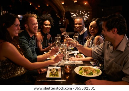 Group Of Friends Enjoying Meal In Restaurant #365582531