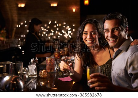 Portrait Of Couple Enjoying Night Out At Cocktail Bar #365582678
