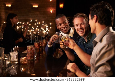 Male Friends Enjoying Night Out At Cocktail Bar #365582699