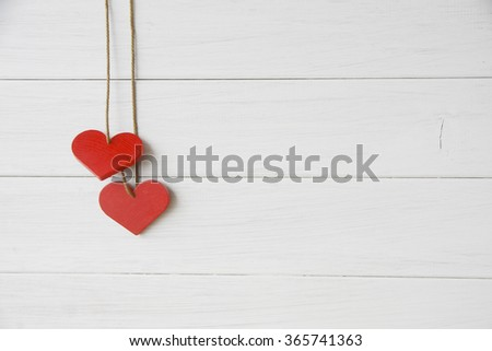 Valentines day wooden hearts on white wooden wall with copy space. Toned #365741363