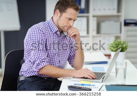 Young businessman in a checked shirt sitting working on a laptop at a table in the office with a thoughtful expression, side view #366215258