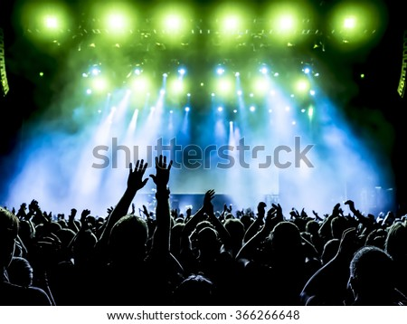 silhouettes of concert crowd in front of bright stage lights Royalty-Free Stock Photo #366266648