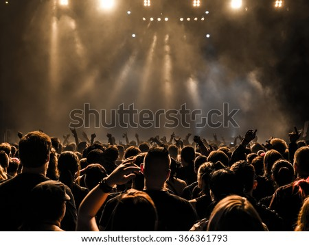 silhouettes of concert crowd in front of bright stage lights Royalty-Free Stock Photo #366361793