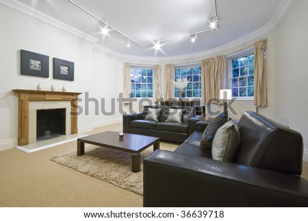 classic living room with a large rounded bay window, furnished with brown leather sofas, and modern decoration