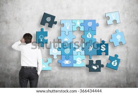 A man with one hand on head, the other in the pocket looking at a puzzle of different business components on a concrete wall, several parts missing. Concept of getting a full picture.