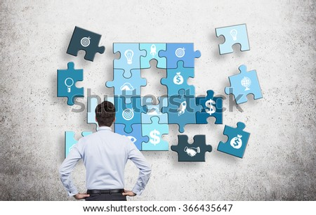 A man with hands on hips looking at a puzzle of different business components on a concrete wall, several parts missing. Concept of getting a full picture.