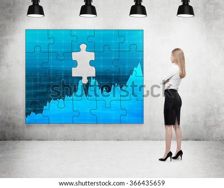 A businesswoman standing with arms crossed in front of a puzzle on the concrete wall with a picture of blue graphs, one part missing, four lamps on the ceiling. Concept of getting the full picture.