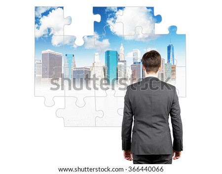 A businessman standing with a stiff back in front of a puzzle on the white wall with a picture of New York, several parts missing. Back view. Concept of getting the full picture.