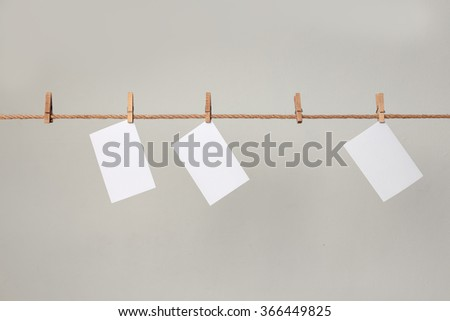 white photo paper. Hanging on a clothesline with clothespins. On a gray background #366449825