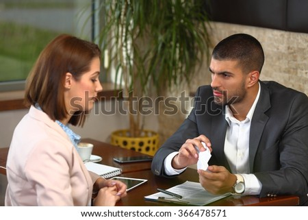 Angry young businessman crumbling some paperwork during the meeting with his colleague in a coffee shop #366478571