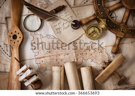 Vintage still-life of old maps, a model of the ship, helm, magnifying glass, old letters on the background of vintage cards
