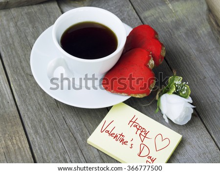 Romantic breakfast on Valentine's Day. Cup of coffee and heart shape cookies, white rose decoration, Happy Valentine's Day message. Toned image