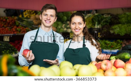 Two positive stuff in apron selling sweet seasonal apples at marketplace #366853373