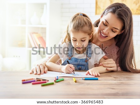 Happy family. Mother and daughter together paint. Adult woman helps the child girl.