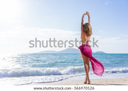 Portrait of young woman wearing a pink sarong and bikini  on the tropical beach  #366970526