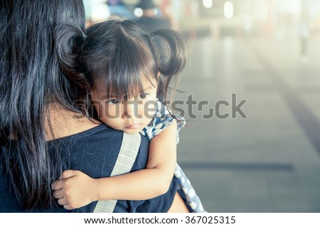 Mother and child,cute little girl resting on her mother's shoulder in the train station, vintage filter effect,selective focus #367025315